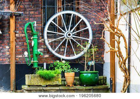 Backyard decoration old wooden cart wheel water pump various decoration material.