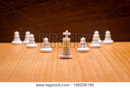 Chess white king and his retinue on a wooden background army and leader