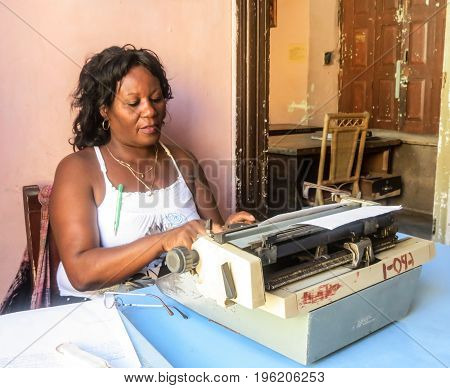 Trinidad de Cuba, Cuba, July 2, 2012; Cuban typist typing on old fashioned manual typewriter in typical office in Trinidad de Cuba