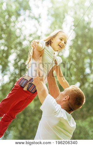 caucasian dad and young daughter playing together in summer park at day time