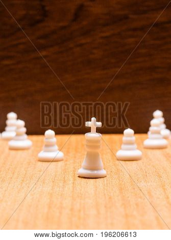 White king and white pawns on a wooden background chess is a very ancient board game that was invented in India nowadays it has become popular all over the world