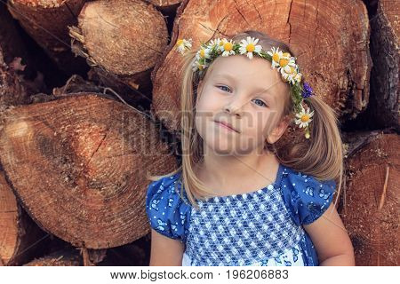 A cute 3 years old girl with chamomile wreath is standing in front of a wood stack