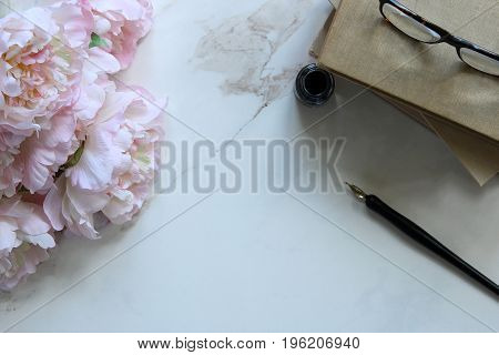 Minimalist styled desktop with peony bouquet, book stack, pen and ink, and eyeglasses. White marble copy space.