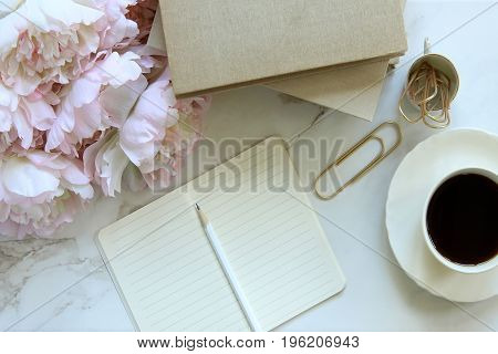 Peony bouquet, book stack, open notebook, and coffee cup styled desktop. Copy space.
