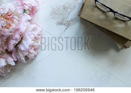 Minimalist styled desktop with a bouquet of peonies, book stack and eyeglasses. White marble copy space.