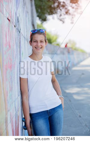 Hipster girl wearing blank white t-shirt, jeans and sunglasses posing against rough street wall, minimalist urban clothing style, mockup for tshirt print store