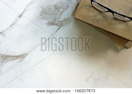 Minimalist white marble desktop with a book stack and eyeglasses. Copy space.