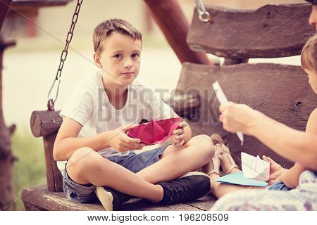 Three member caucasian young family sitting on a wooden swing outdoors on summer day folding a paper boats together.Focus is on boy who is holding a red paper boat and looking into camera.