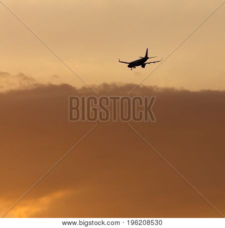 The plane is landing at the yellow sunset