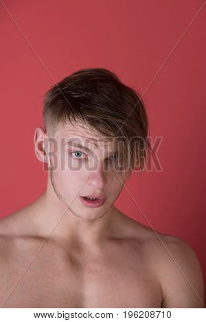Man with handsome face and blond hair posing with bare chest on red background. Fitness. Skincare and hygiene. Beauty and hairdressing salon