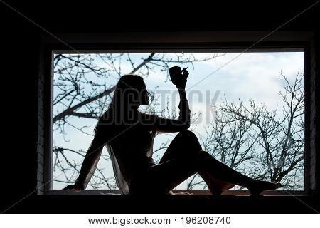 Woman with in dress laying at window. Girl drink from cup in morning. Beauty and fashion. Silhouette of sexy woman on window sill. Fashion model posing.
