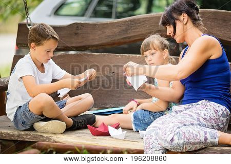 Caucasian three member family sitting outdoors on a big wooden swing. Mother is teaching her kids how to fold a paper boat