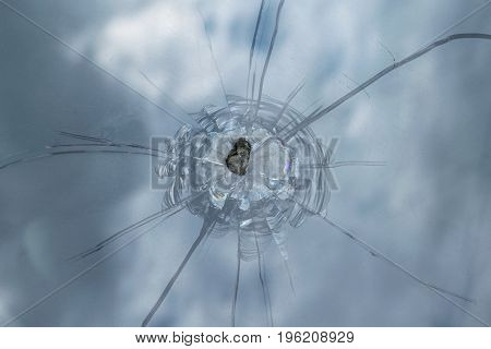 The broken windshield of the car from flying stone. The hole in the glass chips and debris cracks in strips. The glass reflects the sky with clouds.