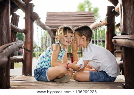 Happy two caucasian siblings sittign in a wooden house outdoors on summer day holding a paper boats in their hands boy whispering a secret into girl´s ear