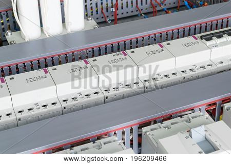 The control Cabinet installed circuit breakers modular contactors capacitors. Automatic switches modular contactors arranged in a row. Wire is laid and hidden in perforated cable tray.
