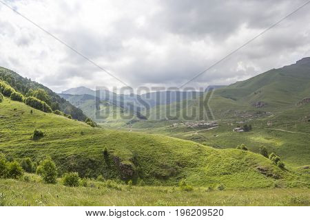 Mountain landscape, beautiful green slopes in the picturesque gorge, the cloudy sky. Nature and mountains of the North Caucasus