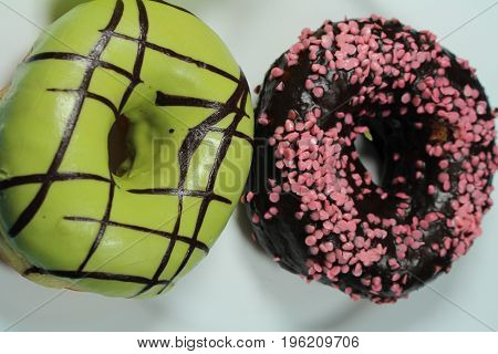 Donuts with green and chocolate icing/ Donuts with green and chocolate icing and pink topping.