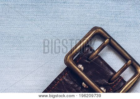 Old leather strap with buckle on denim background