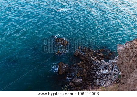 View from altitude on high cliff on the blue sea water and big stones on shore cape Kaliakra in Bulgaria.