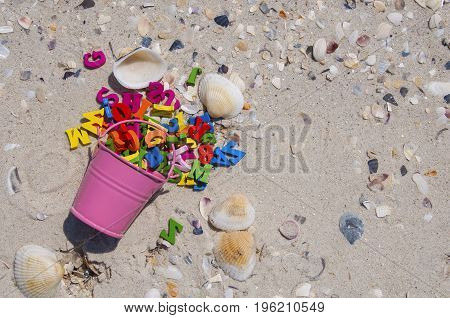 Multicolored wooden letters scattered on a sandy beach with seashells empty space on the right