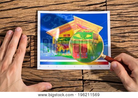 Person Analyzing The Heat Loss And Energy Efficiency Of A House With Magnifying Glass