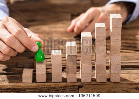 Close-up Of A Businessman Placing The Green Figure On Increasing Block Stack Over The Table