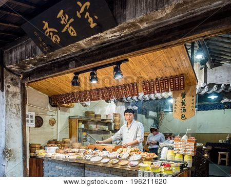 Suzhou, China - Nov 5, 2016: At the historic Zhouzhuang Water Town. A food store in traditional cultural styling selling buns, noodles and other hot foods.