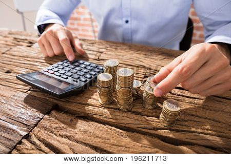 Close Of A Businessman Calculating Coins Using Calculator On Wooden Desk