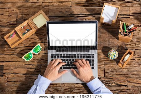 Business People Typing On Laptop At Workplace With Office Supplies Over The Wooden Desk