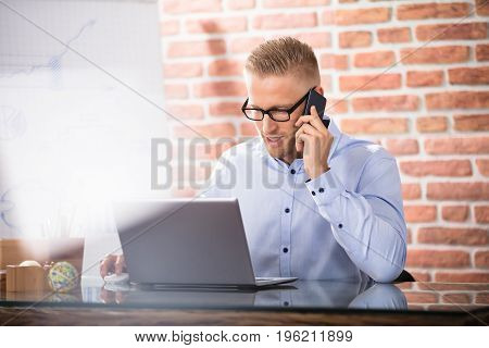 An Attractive Businessman Talking On Cell Phone While Working In The Office