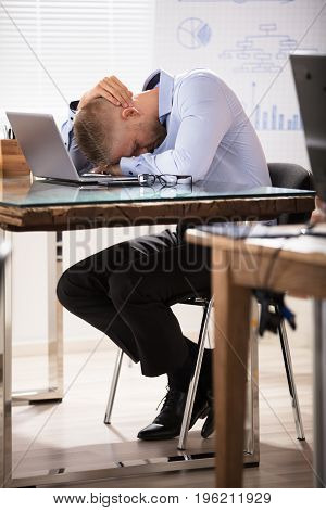 Close-up Of A Businessman Sleeping Over The Office Desk With Laptop