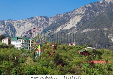 Carousel Ferris wheel in Yalta on the background of the Crimean mountains