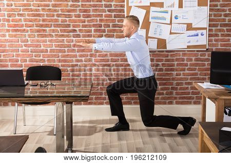Attractive Businessman Doing Exercise In Office Against Brick Wall