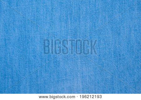 Natural light blue denim texture. Cotton jeans cloth