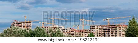 Many building tower cranes. Panoramic review. Construction of the new quarter.