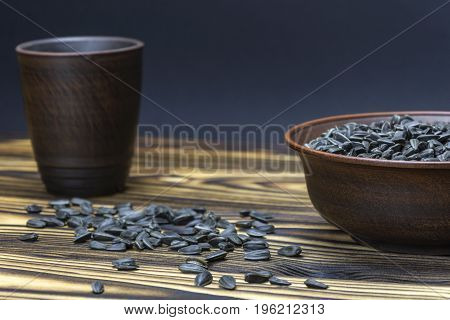 sunflower seeds are in a bowl on a wooden table