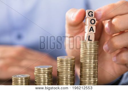 Close-up Of Hand Holding Goal Blocks Over The Increasing Coin Stack