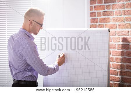 Close-up Of A Businessman Writing On Grid Flip Chart With Marker In Office