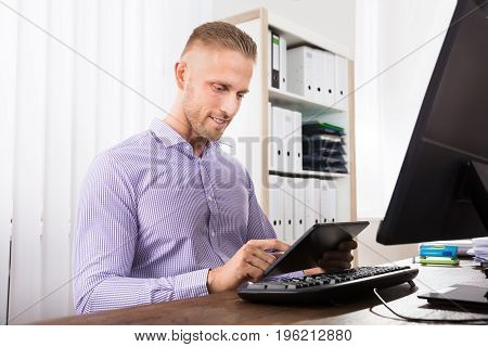 Smiling Businessman Using Digital Table In Front Of Computer At Workplace