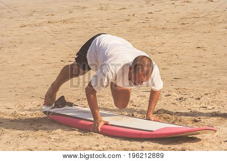 Man learning to surf on the Kuta beach in Bali in Indonesia