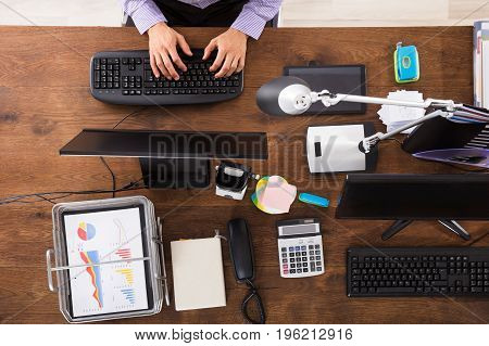 Elevated View Of Businessperson Working On Computer Over Wooden Desk