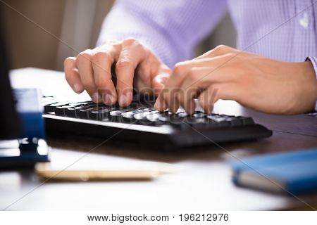 Close-up Of A Businessperson's Hand Typing On Computer Keyboard