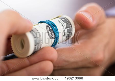 Close-up Of A Person Handing Over The Rolled Up Money To Another Hand