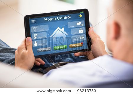 Close-up Of Man Using Home Control System On Digital Tablet