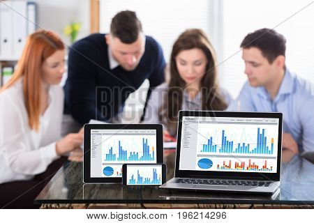 Graph Display On Various Modern Electronic Devices Screen Over The Office Desk