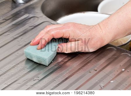 The cook wipes the sink with a rag .