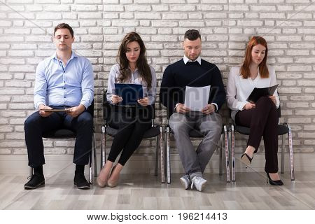 Group Of People Sitting On Chair Waiting For Job Interview In Office