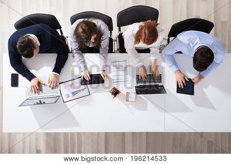 Elevated View Of Business People Using Electronic Devices At Desk In Office