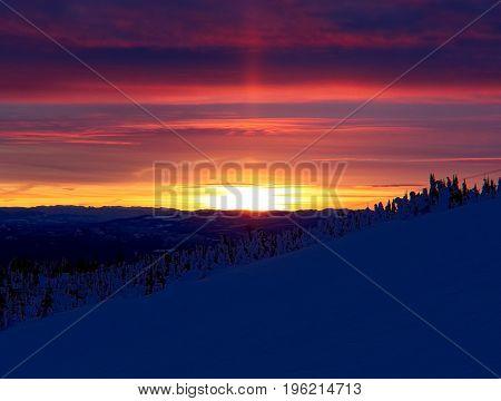 Vibrant Sun Pillar Sunset Over Snow Covered Landscape