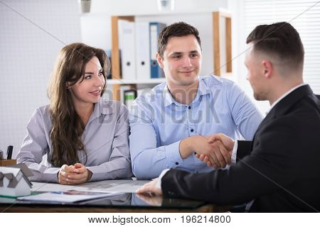 Young Couple Shaking Hands With Architect Or Mortgage Broker